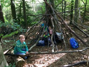 A group of Year 4 boys playing in the den they built during an activity in Forest School at Wepre Park